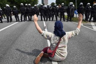 A demonstrator holds her hands up as she faces policemen during a protest on July 7, 2017 in Hamburg, northern Germany, where leaders of the world's top economies gather for a G20 summit