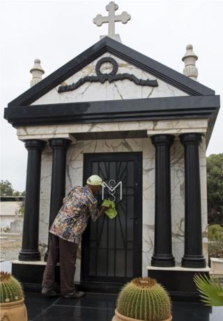 """A man cleans the tomb of Mobutu Sese Seko, the late dictator of the self-styled """"King of Zaire"""", which was later renamed the Democratic Republic of Congo after his overthrow, in the European cemetery in Rabat on September 3, 2017, four days before the 20th anniversary of his death. Mobutu died on September 7, 1997 at the Mohamed V military hospital in Rabat after a long battle with prostate cancer. Twenty years on from his death in exile in Morocco, the simple initials MSS on a family grave mark the resting place of Mobutu Sese Seko, the self-styled """"King of Zaire""""."""