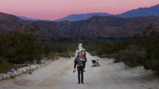 Omar carries Jen on his back in a desert