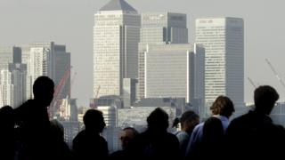 City workers silhouetted in front of the Canary Wharf skyline