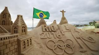 A general view of the Olympic Rings, flag, Vinicius and Christ the Redeemer made into a sand sculpture on the beach during the Olympics preview day