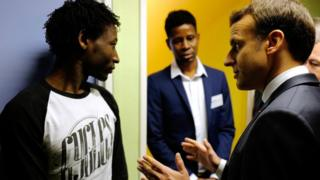 French President Emmanuel Macron speaks to a Sudanese migrant in Calais