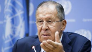 Sergei Lavrov gestures at the camera with a soft-focus UN flag visible in the background