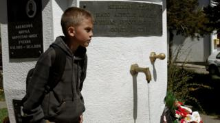 Yeniyetmə oğlan, 1999-cu ildə NATO bombardmanında həlak olan Monteneqro sakinlərinin xatirəsinə həsr edilmiş memorial kompleksə baş çəkərkən.