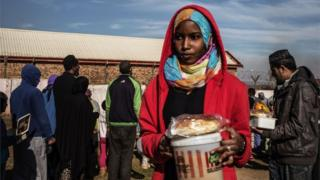 A Muslim woman receives food before breaking the fast for Ramadan in Lenasia, on the outskirts of Johannesburg, on June 26, 2016