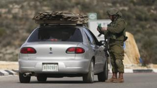 Israeli soldier checks identity papers of a driver at a checkpoint leading to the West Bank city of Ramallah (1 February 2015)