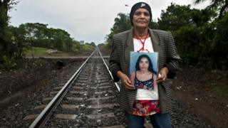 Pilar Escobar Medina holds up a photograph of her daughter Olga, who she last saw in 2009