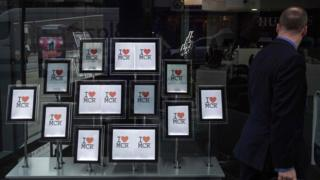 """A man passes a display of """"I love MCR"""" signs in the window of an estate agent""""s in Manchester"""