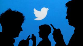 People holding mobile phones are silhouetted against a backdrop projected with the Twitter logo in this illustration picture taken in Warsaw September 27, 2013
