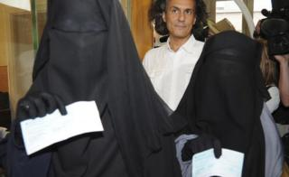 Two women show fines imposed for wearing niqabs in Brussels in 2011. The fines were paid by French businessman Rachid Nekkaz