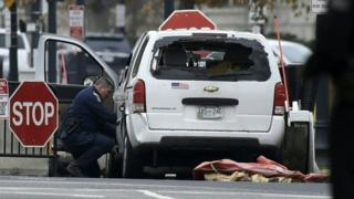 An agent inspects a passenger car sitting at a security barrier it struck near the White House in Washington, DC