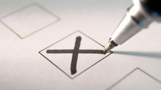 A pen writing a cross in a vote box