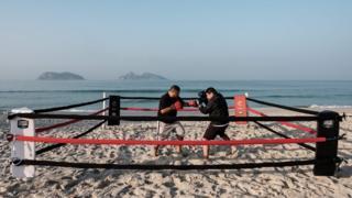 Boxing trainer Moacyr Lima (left) trains Leandro Guignoni in beach boxing at Pepe beach in Rio de Janeiro, Brazil