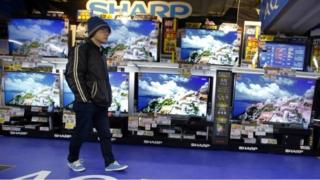 """A shopper walks in front of Sharp""""s Aquos flat-panel TVs at an electronics store in Tokyo, Thursday, Feb. 25, 2016"""