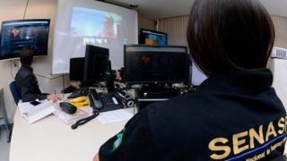 Brazilian police watch on a big screen as anti-paedophile raid unfolds