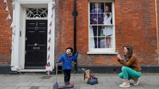 An image of Britain's Prince Harry and his US fiancée Meghan Markle is seen in a window as a woman photographs a child near Windsor Castle in Windsor