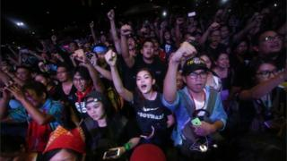 Young people are pictured holding hands up at a night time protest in Manila