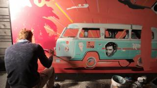 An artist draws an Austin-themed mural at the Australia House's opening night party