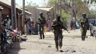 This picture taken on April 30, 2013 shows Nigerian troops patrolling in the streets of the remote northeast town of Baga, Borno State