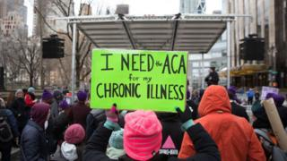 A health care activist lifts signage promoting the Affordable Care Act during a rally at Trump Tower in New York.