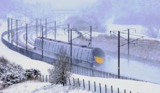 A Eurostar train passes through snow in Ashford, Kent