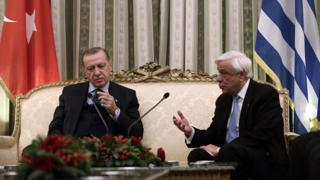 Greek President Prokopis Pavlopoulos speaks with his Turkish counterpart Recep Tayyip Erdogan during a meeting at the Presidential Mansion in Athens