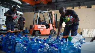 Workers collect bottles of water to distribute to communities with no water in South Africa