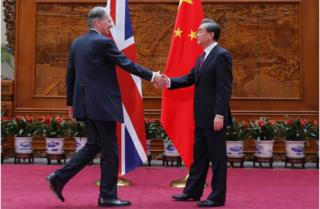 Foreign Secretary Philip Hammond shakes hands with his Chinese counterpart, Wang Yi