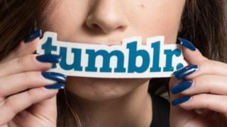 Mujer sostiene sobre la boca un molde de letras que dice Tumblr.