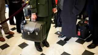 A military aide carries the nuclear football, with the United States' nuclear launch codes