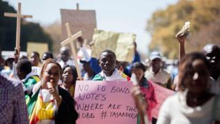 "Protesters in Harare, Zimbabwe, holding crosses and one holding a sign reading ""No to bond notes, where are the jobs"" - Wednesday 3 August 2016"