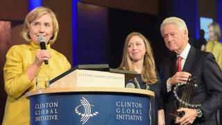 Chelsea and Bill Clinton watch Hillary Clinton at a meeting of the Clinton Global Initiative