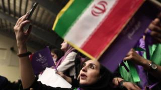 An Iranian woman uses her mobile phone at a campaign rally for Hassan Rouhani in Ardabil (17 May 2017)