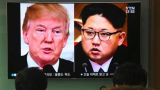 People watch a television news report showing pictures of US President Donald Trump (L) and North Korean leader Kim Jong Un at a railway station in Seoul on March 9, 2018