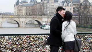 young couple kiss on a bridge