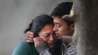 Family members of plane crash victims cry as they wait to receive their bodies in Kathmandu (25 February 2016)
