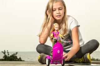 Young girl playing with doll on Segway-style scooter