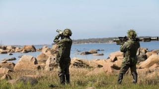 A press release photo of soldiers on a training exercise by the sea