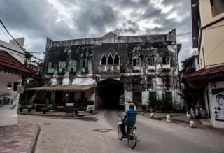 Mwanamume anapeleka baiskeli mjini Zanzibar