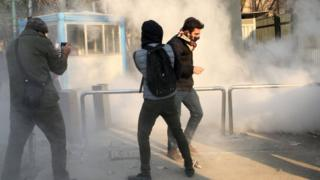 Iranian students run for cover from tear gas at the University of Tehran during a demonstration