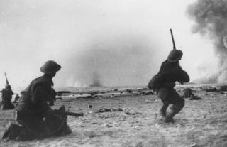British soldiers fight a rearguard action during the evacuation at Dunkirk, shooting rifles at attacking aircraft. Bombs are exploding in the sea. The Dunkirk evacuation, codenamed Operation Dynamo by the British, was the evacuation of Allied soldiers from the beaches and harbour of Dunkirk, France, between 26th May and 4th June 1940.