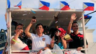 Mr Duterte raising his fist to supporters at at rally in Cainta Rizal on 12 April
