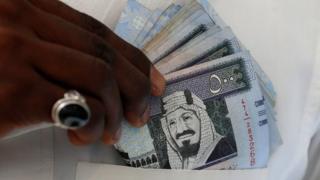 Саудовские банкноты в руках