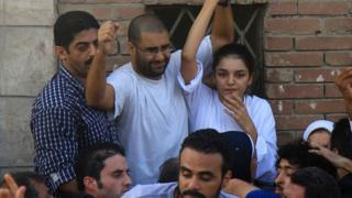 Sanaa Seif (R) and Alaa Abdel Fattah (C) raise their hands after being released from prison for the funeral of their father (28 August 2014)