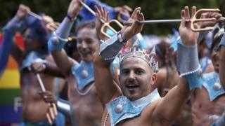 Participants in silver crowns and carrying tidents prepare for the annual Gay and Lesbian Mardi Gras parade in Sydney, Saturday, March 4, 2017.