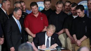 Donald Trump firma la orden ejecutiva.