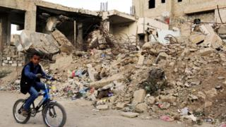 A Yemeni boy cycles past a house destroyed in an air strike in Sanaa, Yemen (21 November 2016)