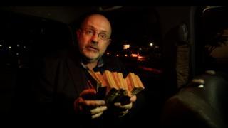 John Sweeney holds a stack of Venezuelan Bolivars