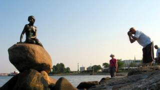 A man photographs the Little Mermaid statue in Copenhagen