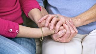 An older and younger woman holding hands